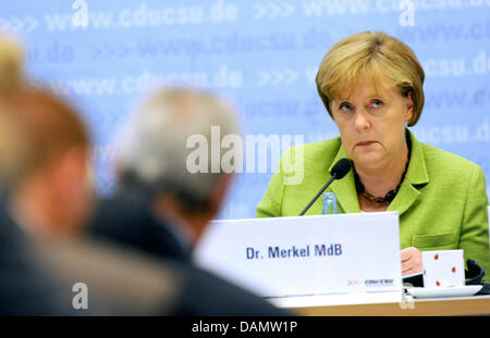 German Chancellor Angela Merkel (CDU) sits on the podium as she speaks during the congress meeting of the CDU and - Stock Photo