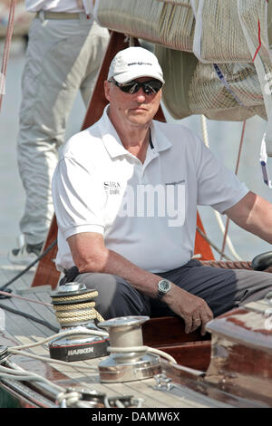 King Harald V of Norway sits at the helm of his boat Sira at the Quellental marina in Gluecksburg, Germany, 29 June - Stock Photo