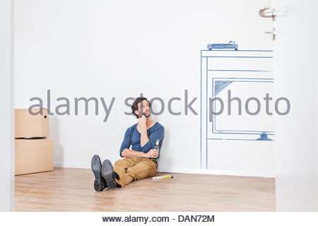 Man thinking about furnishing new living room - Stock Photo