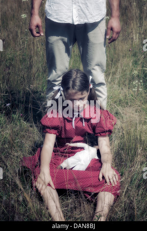 a sad girl sitting on a field, a man is standing behind her - Stock Photo