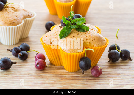 Muffins filled with currant decorated with mint - Stock Photo