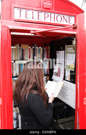 Reader in de-commissioned British Telecoms telephone box transformed into a community book exchange, Little Eaton, - Stock Photo