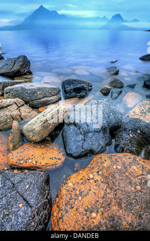 Sunrise at elgol on the Isle of Skye with mountain mist and a rocky shore. - Stock Photo