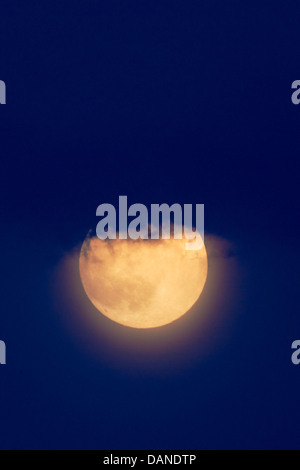 Forest fire smoke colors the full moon rising over Rocky Mountains. - Stock Photo