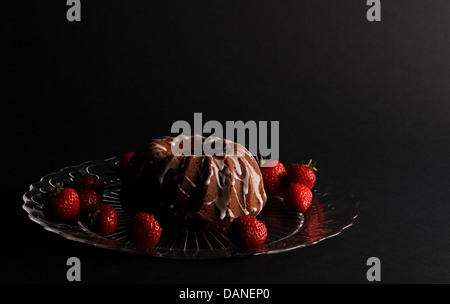 Chocolate pound (bundt) cake icing and strawberries on glass plate and dark background - Stock Photo