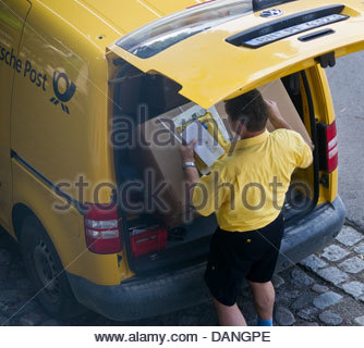 German Post Office picking up large box parcel carrying weight heavy - Stock Photo
