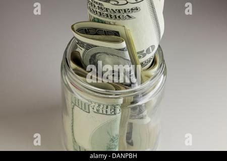 Money stuffed in small glass jar - Stock Photo