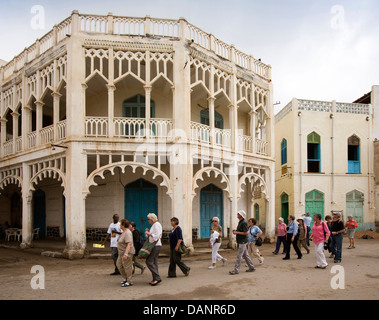 Africa, Eritrea, Massawa, Old Town, group of cruise ship passengers passing Ottoman architecture building - Stock Photo