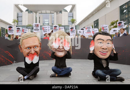 Dressed as Foreign minister Westerwelle (L), Chancellor Merkel (C) and Economy Minister roesler (R) activists of - Stock Photo