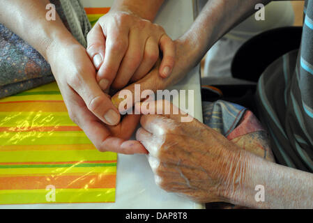 Nurse for the elderly Kirsten Kausch holds the hands of a resident at Marie-Schmalenbach-House in Herford, Germany, - Stock Photo