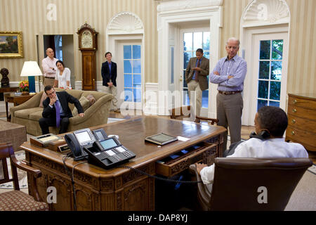 HANDOUT - President Barack Obama talks on the phone with House Minority Leader Nancy Pelosi in the Oval Office to - Stock Photo