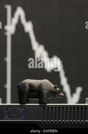In front of a falling German DAX stock index a black miniature bear stands on a monitor at the stock exchange in - Stock Photo