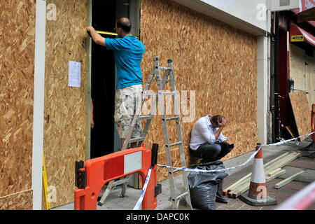 A man covers the windows of a shop with wooden planks while his colleague is sitting on the ground after riots in - Stock Photo