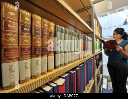 Student Roxana Ajib (25) reads passages of a book volume of Kleist at the Thuringian University and State Library - Stock Photo