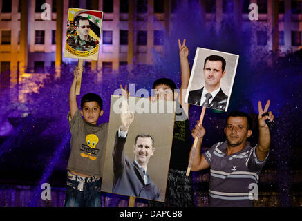 A man and his two children show posters of Assas as they demonstrate in support of Syrian Pressident Bashar al-Assad - Stock Photo