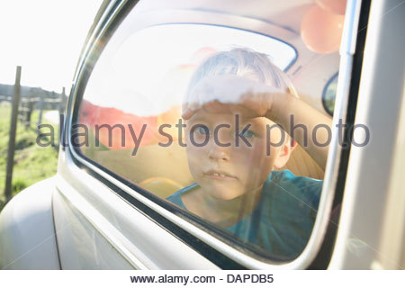 Germany, North Rhine Westphalia, Cologne, Boy in car looking through window - Stock Photo