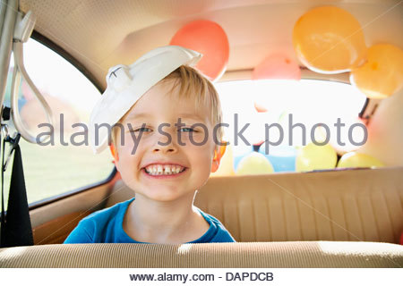 Germany, North Rhine Westphalia, Cologne, Portrait of boy in car with easter bunny mask, smiling - Stock Photo