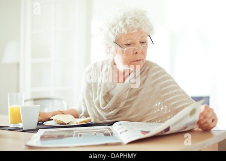 Relaxed senior woman having her breakfast and reading the morning news - Stock Photo