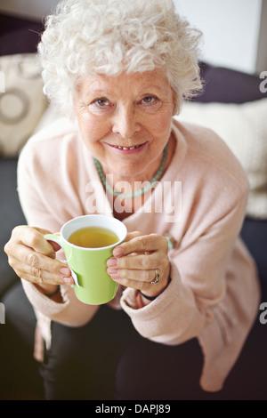 Indoor senior woman enjoying her tea and smiling at you - Stock Photo