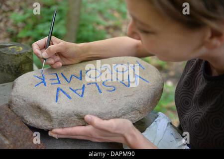 A councellor the summer camp Action Reconciliation Service for Peace (ASF) paints a memorial stone to be placed - Stock Photo