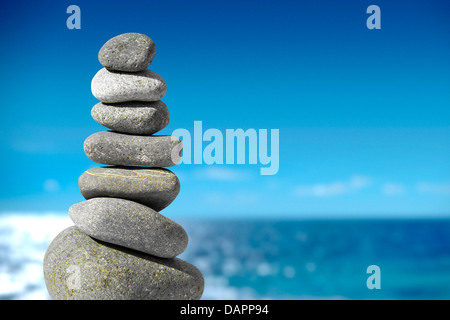 Balance on blue, Stone balance pebble stones on beach with sea in background - Stock Photo