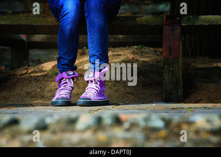 Trendy, hot pink high top sneakers worn with tight jeans on a woman sat down on a  fence. - Stock Photo