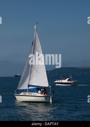 Yacht and Motorboat heading out to sea, Plymouth, UK 2013 - Stock Photo
