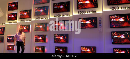 A man walks past a wall with televisions at the International Radio Exhibition IFA at the exhibition grounds in - Stock Photo