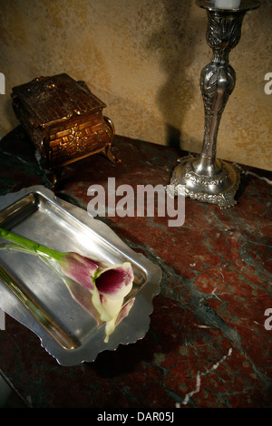 still life on marble surface, ornamental box, silver candle holder, silver tray and flower - Stock Photo