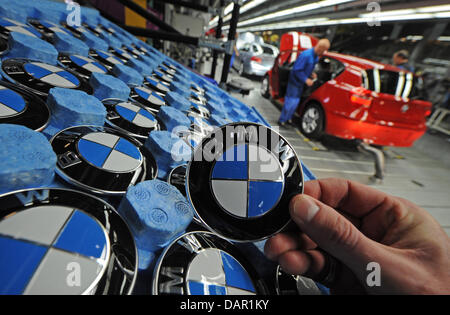 (FILE) An archive photo dated 08 November 2010 shows an employee holding up a BMW emblem in a factory in Regensburg, - Stock Photo