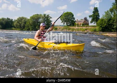 Canoeist in kayak type yellow canoe on the River Wye at The Warren, Hay on Wye, Powys, Wales, UK - Stock Photo