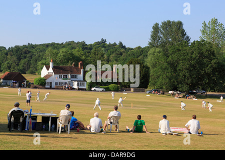 Local team playing a cricket match on village green in front of Barley Mow pub on a summer's evening. Tilford Surrey - Stock Photo
