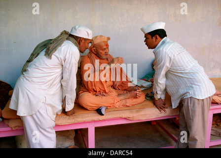 Two hindu men are listening with attention what an old ascetic ( sadhu) is saying. All of them belong to the Swaminarayan - Stock Photo