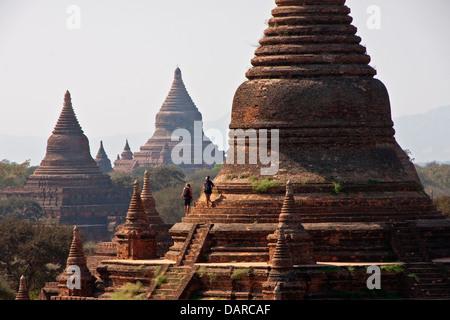 Climbing tourists exploring Buddhist pagodas on Bagan Plains. - Stock Photo
