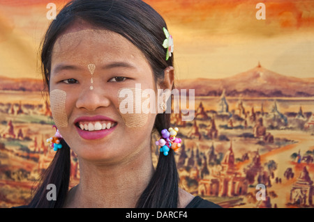 Young woman with thanaka-bark make-up with painting of pagodas on Bagan Plains in background. - Stock Photo