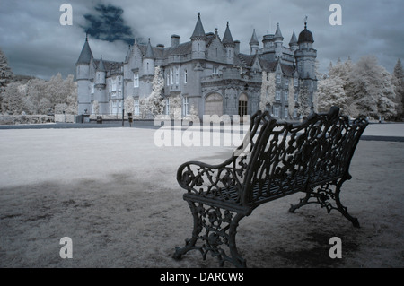 Infrared image of Balmoral Castle, Scotland with garden bench in foreground. HRH Queen Elizabeth and family spend - Stock Photo
