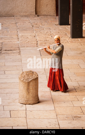 Israel Jerusalem Old City Jewish Quarter The Cardo pretty young orthodox girl long skirt playing flute flautist - Stock Photo