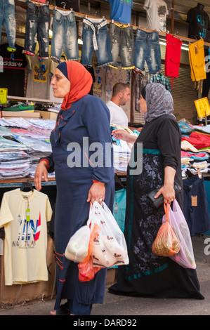 Israel Tel Aviv Carmel Market childrens' clothes stall shop store Arab women ladies shopping in hijab thorb thobe - Stock Photo