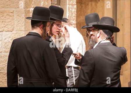 Israel Jerusalem Old City black hat group of ultra orthodox Jewish men Chabad Lubavitch Hasidic forelocks payot - Stock Photo