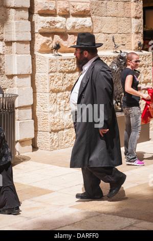 Israel Jerusalem Ultra Orthodox Jewish Hassidic bearded man walking in modern contemporary stylish Alrov Mamilla - Stock Photo