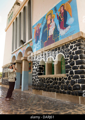 Africa, Eritrea, Massawa, Tualud, St Mary's Cathedral Church western tourist photographing Virgin Mary painted mural - Stock Photo