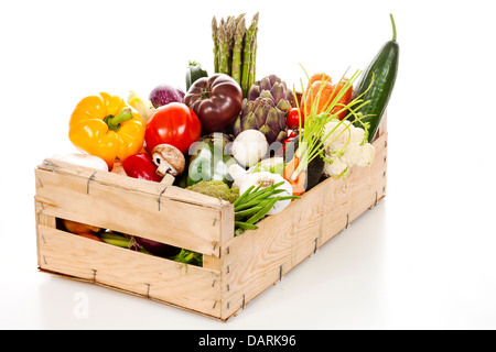 Assortment of fresh vegetables in a crate on white background - Stock Photo