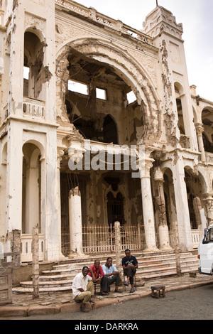 Africa, Eritrea, Massawa, Old Town, men sat outside Banco d'Italia, former bank, battle damaged structure - Stock Photo