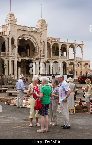 Africa, Eritrea, Massawa, Old Town, people selling souvenirs outside Banco d'Italia, battle damaged former bank - Stock Photo