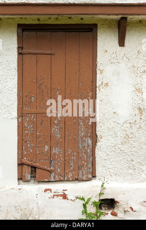 A door on an old building with peeling brown paint in the UK - Stock Photo