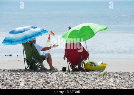 A elderly couple relaxing and chatting whilst sitting under parasols on a warm  windy shingle and sandy beach in - Stock Photo