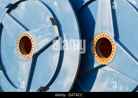 Two big metal spools with hole for drive shaft - Stock Photo
