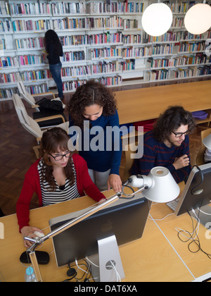 Two women using an Apple iMac computer in library - Stock Photo