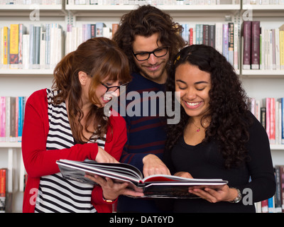 Multi ethnic group of people reading book in a library - Stock Photo
