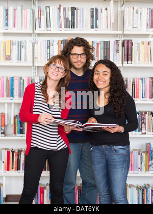 Multi ethnic group of people holding book in a library - Stock Photo